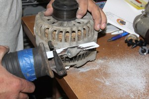 10. The alternator must be modified to fit. These ears (one of each side) were removed with a recip saw and cleaned up with a die grinder. You also have to separate the lower water return hardlines (which run under the manifold and modify another bracket.