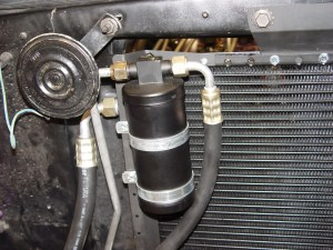 3.The drier and condenser coils are mounted in front of the radiator using the supplied brackets. The hoses are threaded onto the drier and condenser at this time.