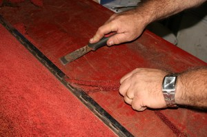 12.Most of the carpet will come off easily, but there will be some that wants to stay. A flat blade scraper makes quick work of it. The hinged area is better left in place, so use the scraper and pull on the edges that is left underneath the trim to remove it.