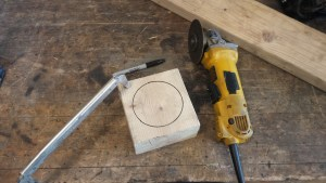 """Two squares of 2x6 screwed together from the bottom and clamped to the table. Make sure to use shorter screws toward the center to keep from interfering with the bowl shape being carved into the top. A circle is drawn on the top as a guide for the bowl. Stay at least a ½"""" from the edge to minimize breaking during use of the block."""