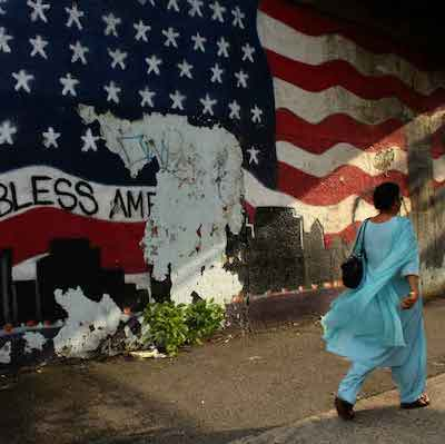 person in Queens in front of flag
