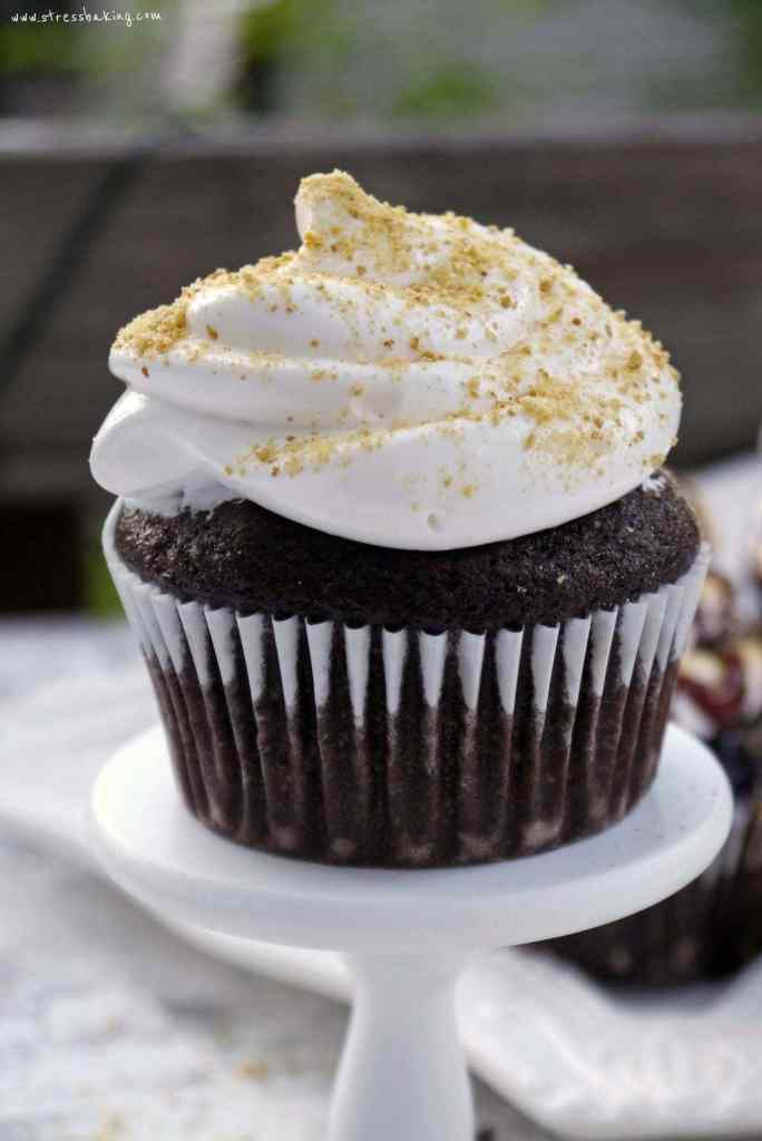 S'more Cupcakes: A favorite campfire treat turned cupcake! Moist chocolate cake is topped with marshmallow frosting and graham cracker crumbs. Get crazy and add some mini marshmallows, chocolate chips and syrup! | stressbaking.com