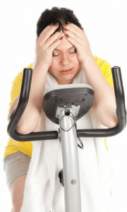exhausted women on exercise bike doesn't see her weight going down from exercise