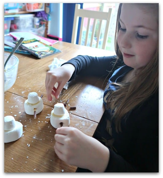 Building a snowman to go on top of our snowman cupcakes