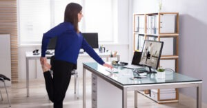 woman standing at desk performing leg stretch