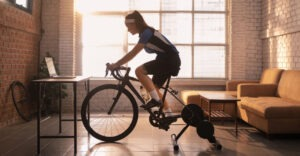 woman at home in apartment setting using stationary bike in front of laptop