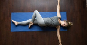woman performing yoga pose while laying on back - half spinal twist