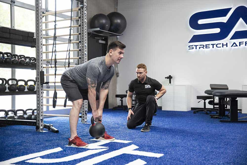 mobility expert kneeling in gym informs form of client performing a deadlift with a medium sized kettle bell