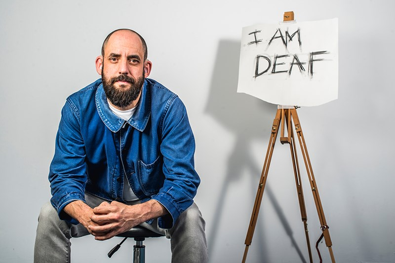"""A man sits next to an easel on which is a piece of paper with the text """"I AM DEAF"""" scrawled on it."""