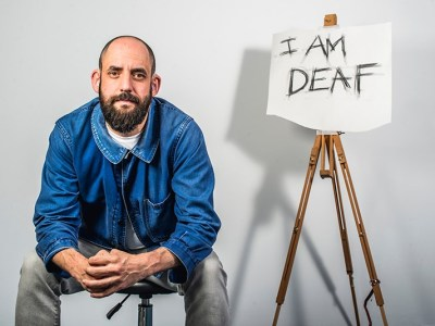 "A man sits next to an easel on which is a piece of paper with the text ""I AM DEAF"" scrawled on it."