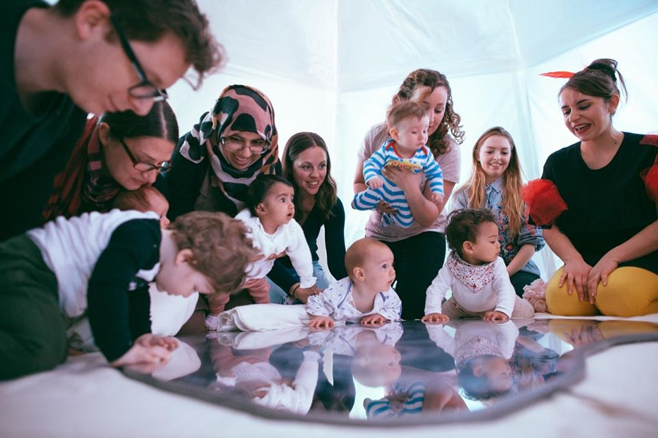 In a white tent, adults and babies alike are enjoying a performance.