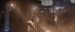 A group of people wear shiny coats and VR headsets. They move in a space surrounded by scaffolding topped with lights.