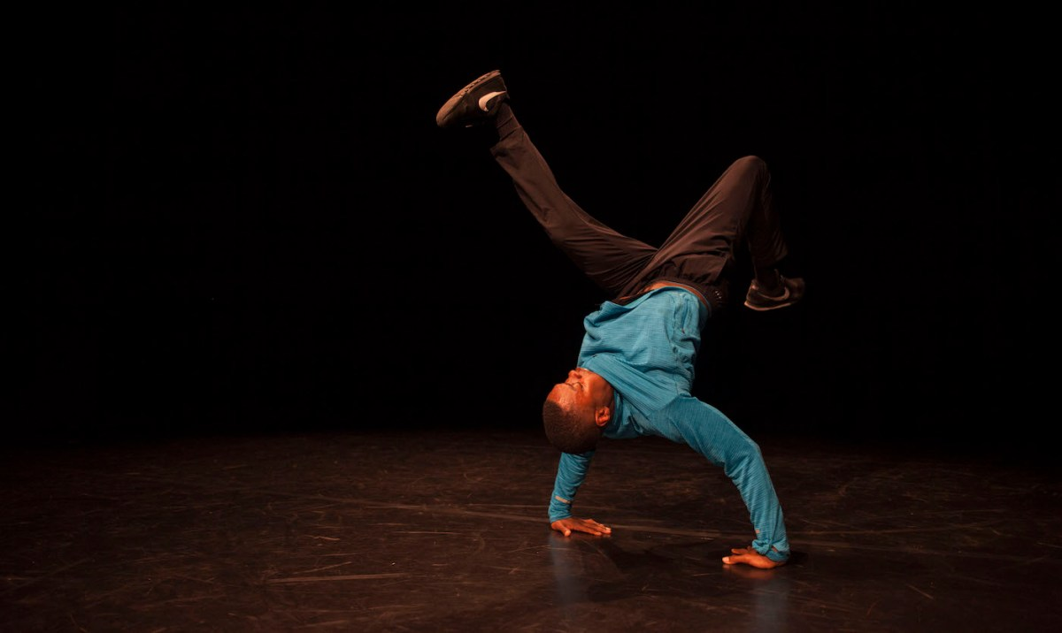 A person does a handstand in a dark studio.