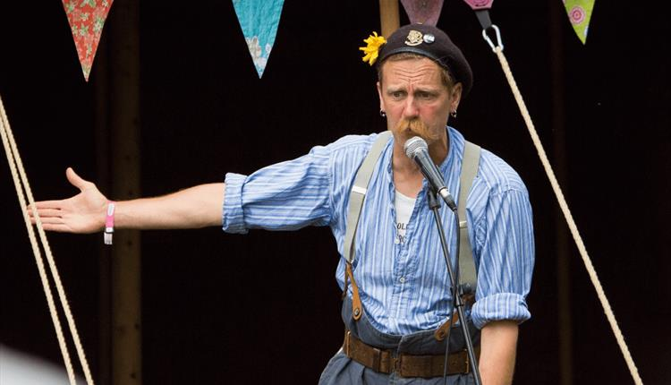 A person with a large moustache stands behind a microphone. Bunting hangs overhead.