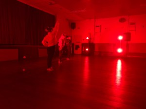 A community centre. Lights cast a strong red glow over the room. Three performers dance in the empty space.
