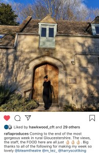 "A screenshot of an Instagram post. The post features a person in front of Hawkwood, a country house. This person in on a mobile 'phone and stands in front of a large wooden door. The picture is captioned ""rafiaproduces: Coming to the end of the most gorgeous week in rural Gloucestershire. The views, the staff, the FOOD here are all just (three okay hand sign emojis). Big thanks to all of the following for making my week so lovely @bteamtheatre @m_tez_ @harryscottking"""