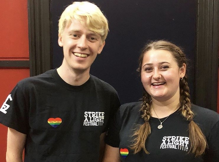 "A man and a woman smile at the camera. They wear black t shirts with a ""STRIKE A LIGHT FESTIVAL"" logo on them. They are also wearing heart shaped stickers with the Pride flag on them."