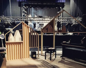 A theatre space. In the background is a large amount of theatre lights. In front of that is a small set, the set contains timber frames that resemble houses, a lamp, some speakers and a piano.