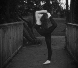 A person practices what this writer believes is an act of contortion. They appear to be on a bridge.