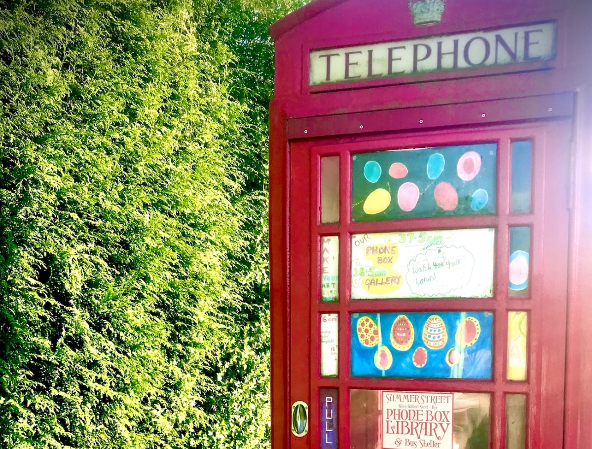 The top half of a red telephone box next to a green hedge. There is simple artwork in the windows of the telephone box.