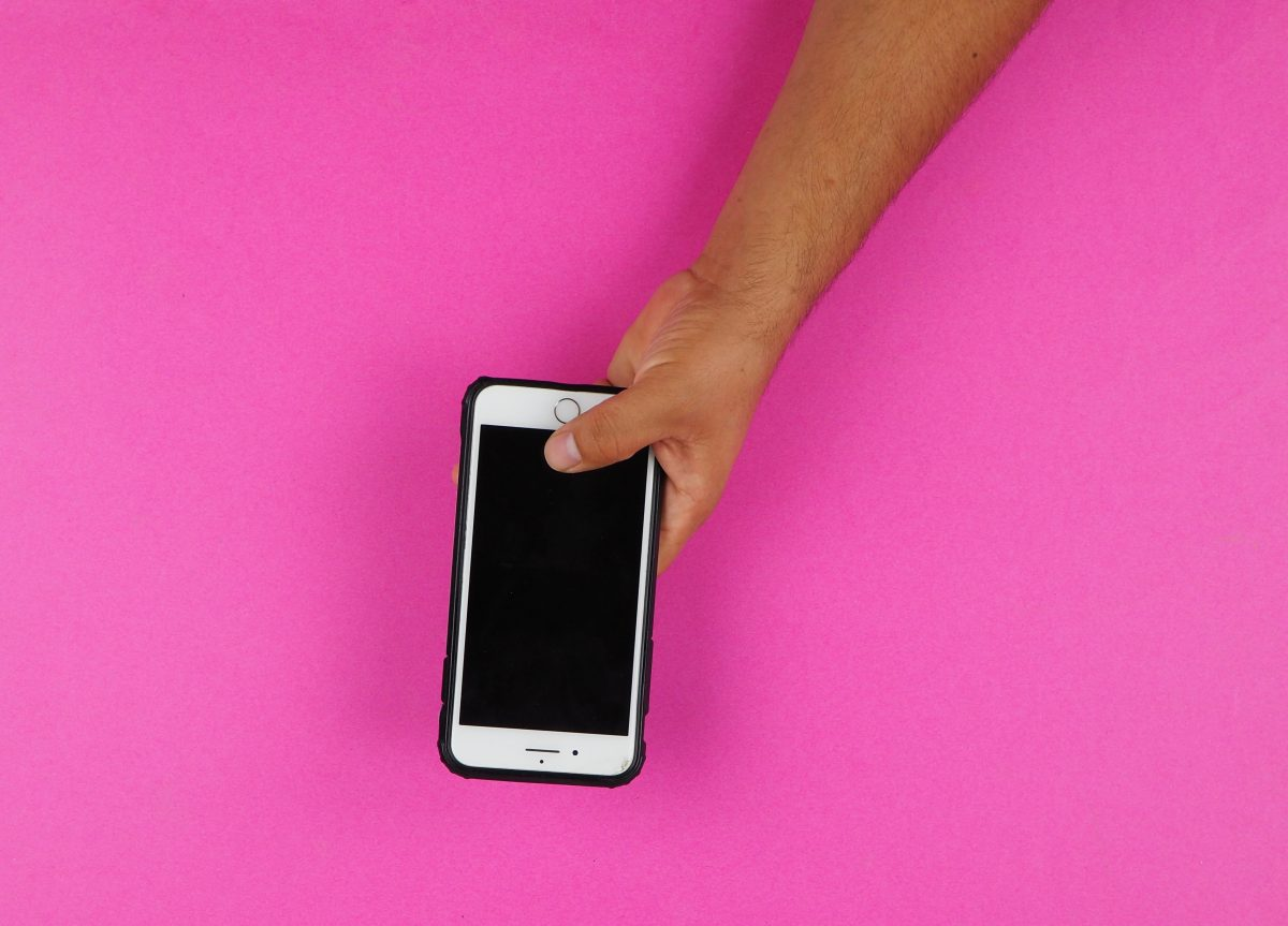 An iPhone held in a hand against a bright pink background.