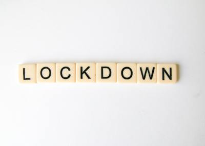 The word lockdown spelled out in scrabble tiles against a white background.