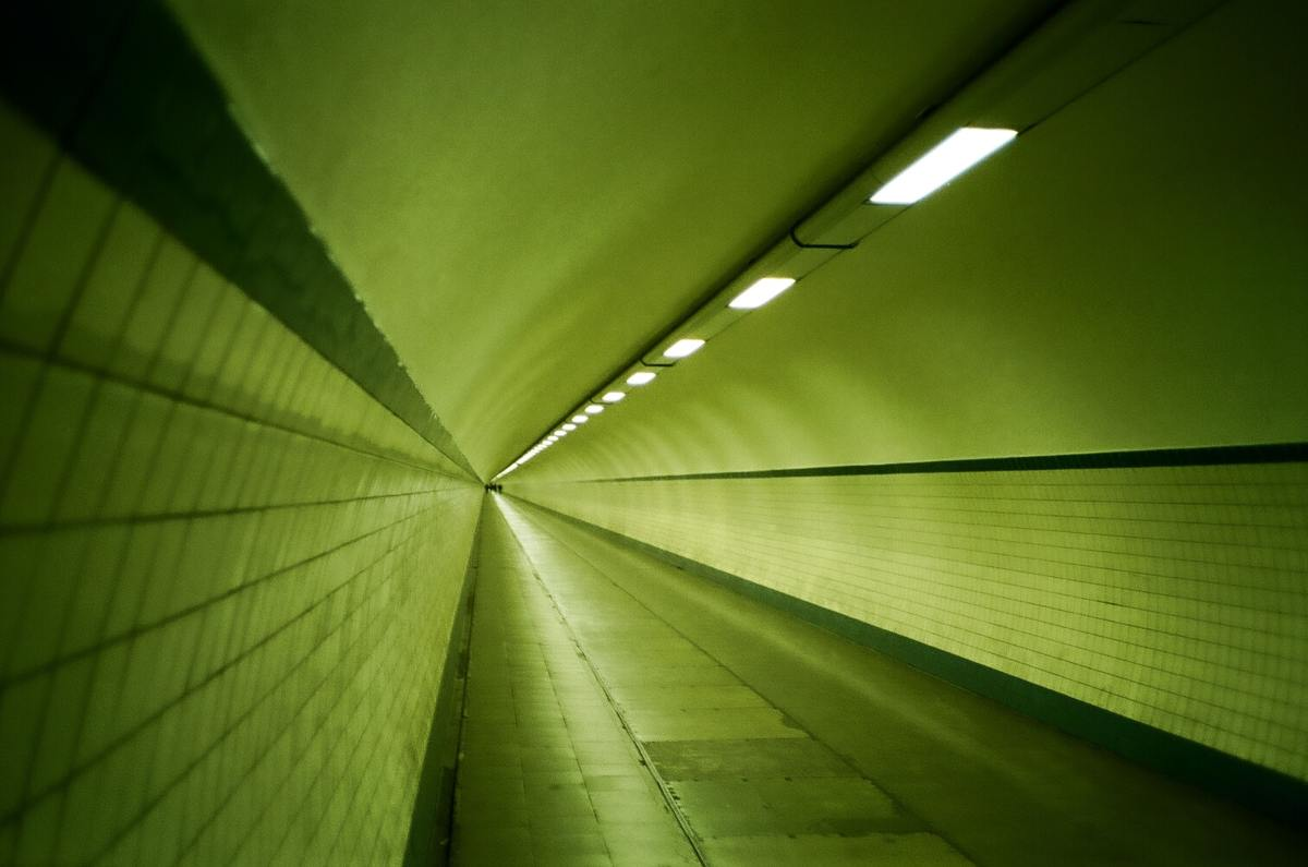 A green coloured empty underground pedestrian tunnel.