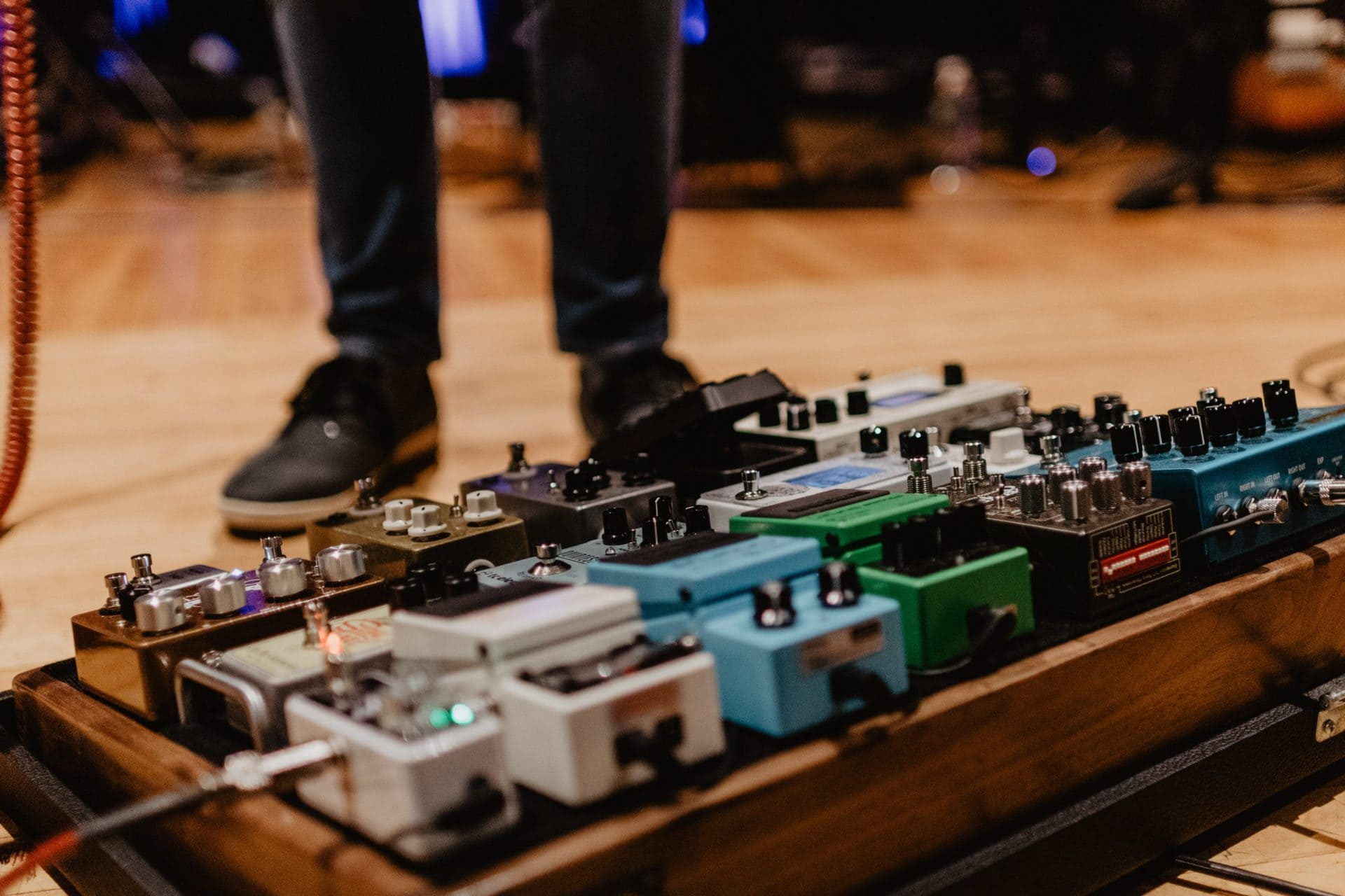 Guitar Player Looking Down at Wah Pedal on Pedalboard