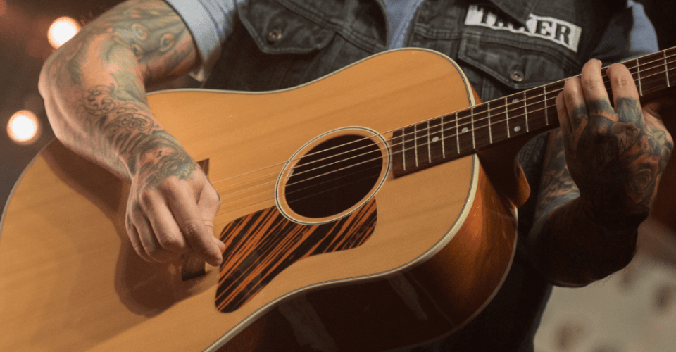 Man playing one of several acoustic guitar body shapes