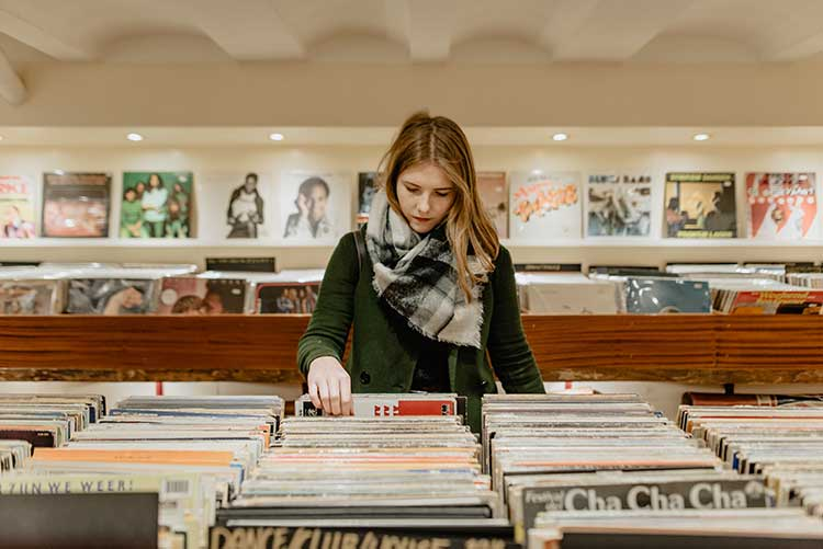 a girl sorting through music at a record store