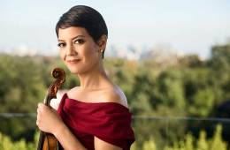 violinist Anne Akiko Meyers holds her violin in a field