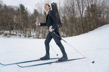 man on skiis with violin case strapped to his back