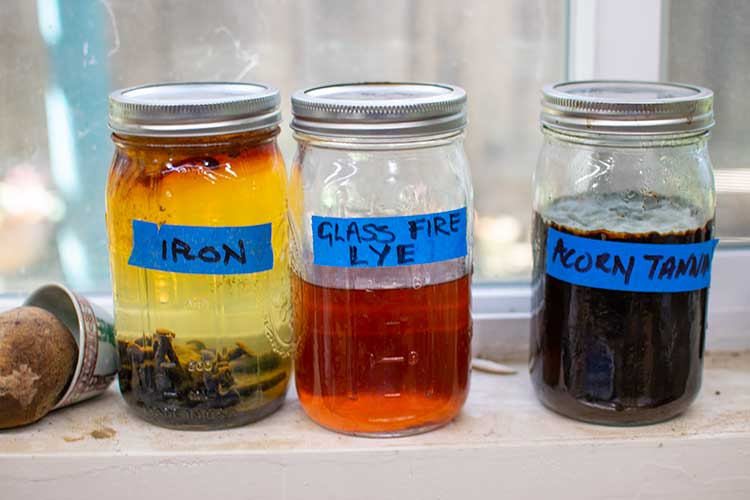 Three jars of Carruthers' homemade dyes: Iron, glass fire lye, and acorn tannin