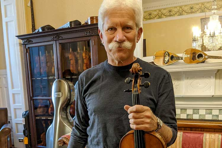 Adult violin player Fred Oster holds up a violin