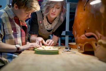 Luthier Rozie DeLoach at the workbench working on an instrument