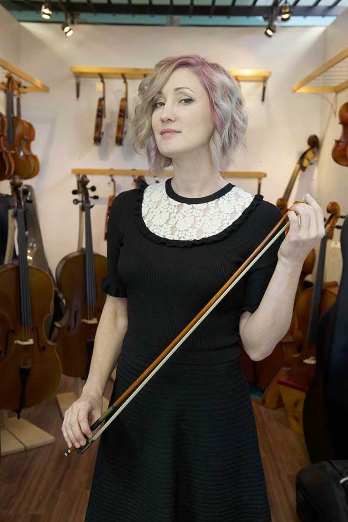 Luthier Rozie DeLoach holds a bow against a wall of instruments