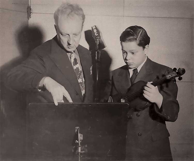 Leopold Stokowski and Kenneth Gordon, age 12, preparing to play the Lalo Symphony espagnole with the NBC Symphony, 1942