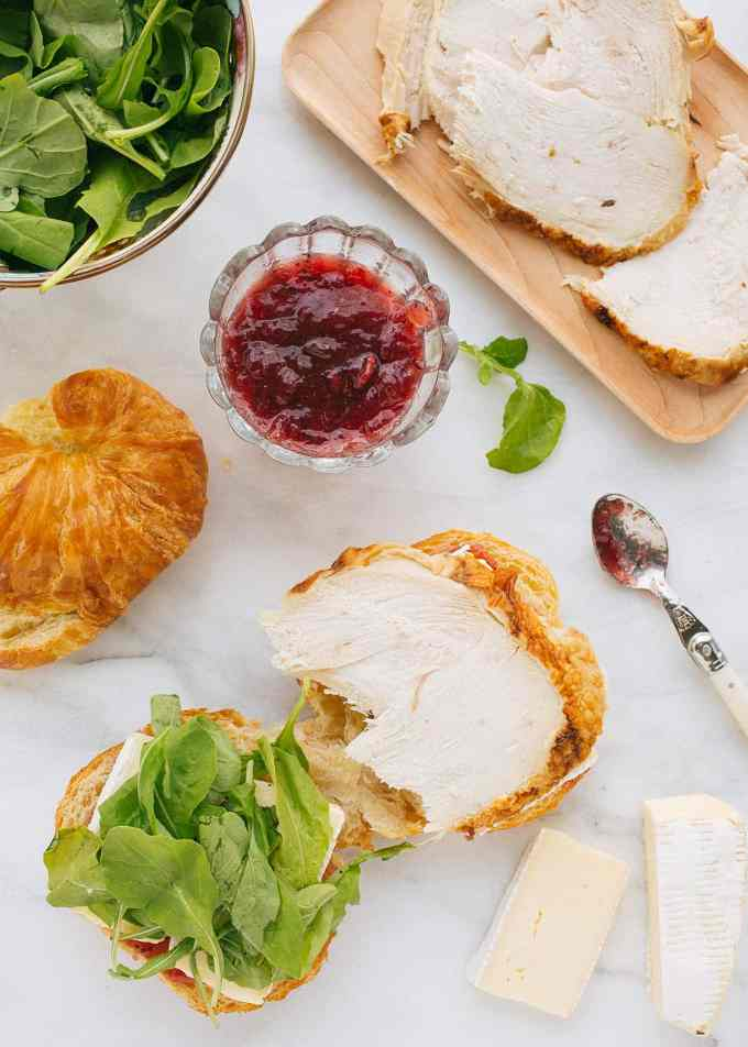 ingredients to make a turkey croissant panini with baby arugula, cranberry sauce, and brie