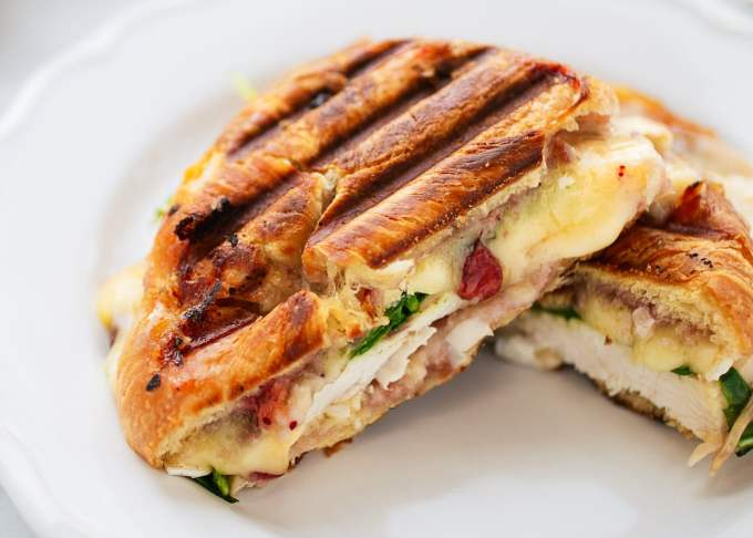 Turkey Croissant Panini with melted brie and cranberry sauce cut in half on a white plate