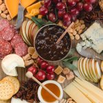 closeup view of a cheese board with fresh fruit and charcuterie