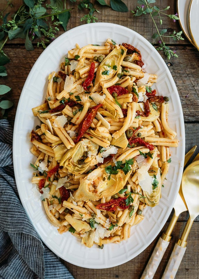 artichoke pasta salad recipe with sun-dried tomato vinaigrette on a white serving platter