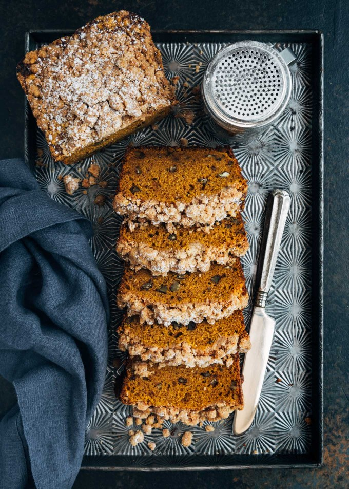 slices of streusel topped pumpkin bread on a baking sheet