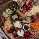 overhead of a fall cheese board assembled on a large round pine charcuterie board