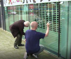 Tekenaars tekenen op de ruit van het stripmuseum Rotterdam, later volgde een kort geding.