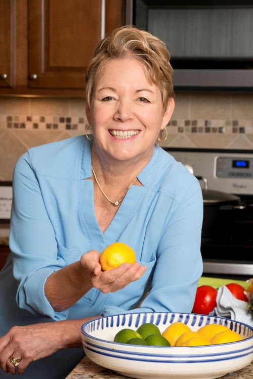 Image of Cathy Brophy, a smiling woman with blond har. She is holding a lemon and has a bowl of lemons and limes in front of her.