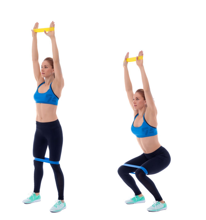 Woman doing overhead squat with exercise bands around hands and knees