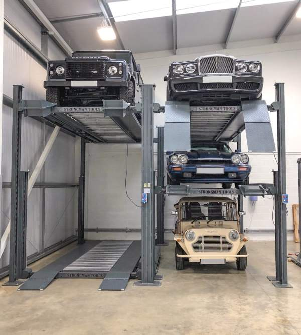 Two double car lifts next to each other. One is lifting a four wheel drive car, the other is holding two older cars with a third older car underneath.
