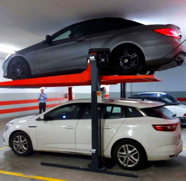 A black and red car lift, holding a grey car with a white car below.