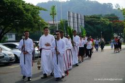 The altar servers, EMCs, Fr Cosmas Lee and some churchgoers going to the hall ahead of the celebration.