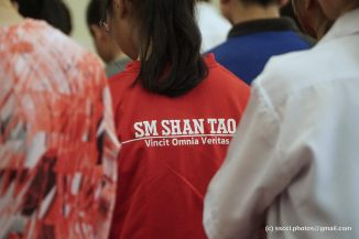 "A student wearing the school's shirt with the words in Latin, ""Vincit Omnia Veritas (Truth Conquers All Things)""."